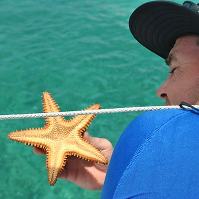 Caribbean guest on a boat holding a starfish
